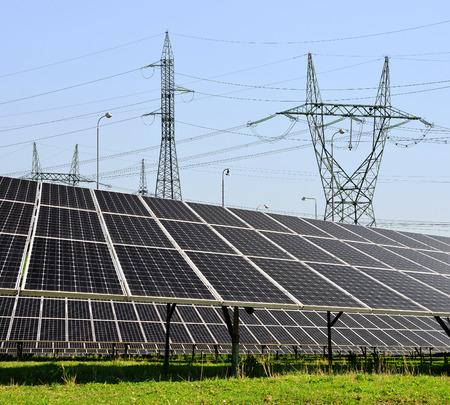 electricidad industrial: Los paneles solares con torres de alta tensi�n Foto de archivo