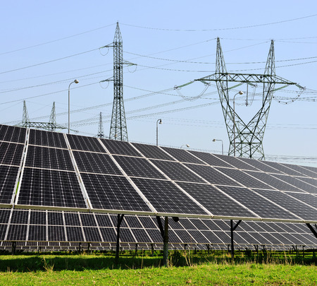 outdoor electricity: Solar panels with electricity pylons Stock Photo
