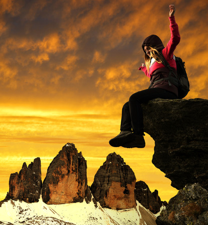 dolomite: Girl sitting on a rock, in the background Tre Cime di Lavaredo at sunset ,Dolomite Alps, Italy