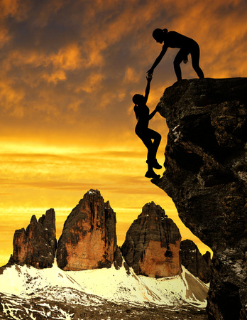 Silhouette of girls climbing on rock at sunset. In the background Tre Cime di Lavaredo ,Dolomite Alps, Italy Stock Photo