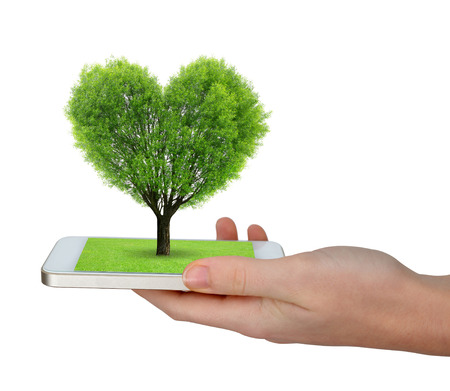 Hand holding a smartphone with a tree in the shape of heart photo