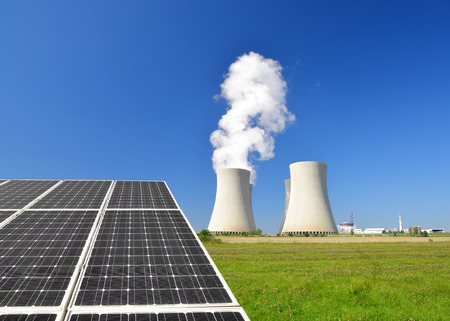 Nuclear waste: Solar energy panels and nuclear power plant Stock Photo