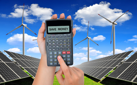 energy saving: Hand with calculator. In the background solar energy panels and wind turbines.Concept of saving money. Stock Photo