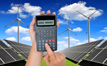 energia solar: Mano con calculadora. En paneles de energ�a solar y e�lica turbines.Concept fondo de ahorro de dinero. Foto de archivo