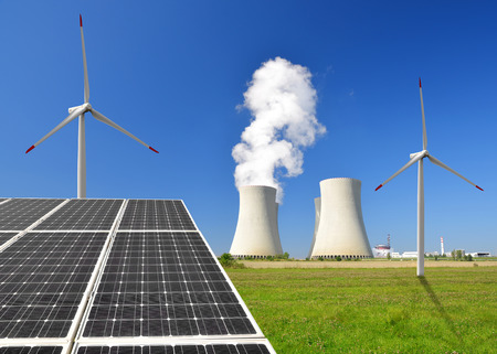wind power plant: Solar energy panels before a nuclear power plant and wind turbines Stock Photo