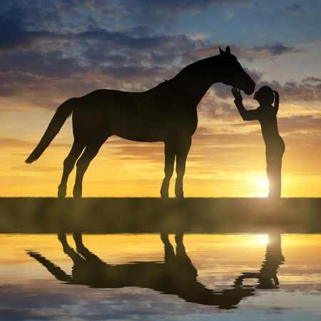 girl on horse: Silhouette of a girl giving a kiss horse in sunset