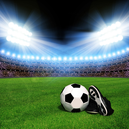 soccer cleats: Soccer ball and shoes in grass, soccer stadium with the dright lights Stock Photo