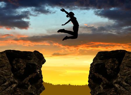 Sylwetka dziewczyny skoków przez szczelinę o zachodzie słońca