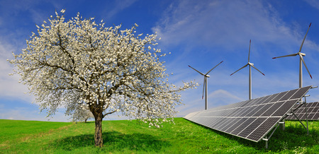 silicium: Solar energy panels with wind turbines and blooming tree in spring landscape. Green energy.