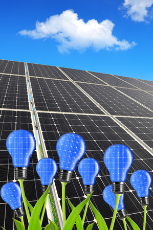 silicium: Solar energy panels with light bulb on plant. Green energy concept. Stock Photo