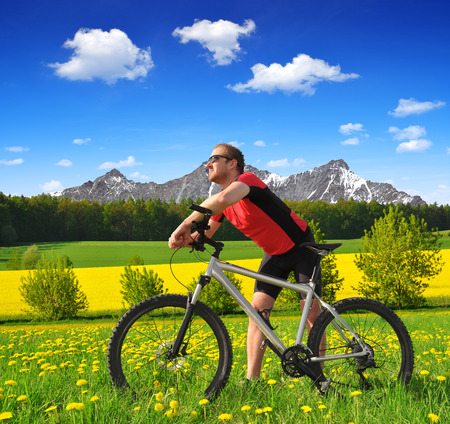 Cyclist with the mountain bike in spring landscape photo