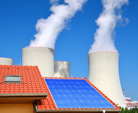 radiacion solar: El panel solar en el techo de la casa en el fondo de la planta de energía nuclear.