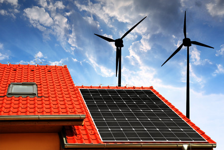 alternativ: Solar panel on the roof of the house in the background wind turbines at sunset.