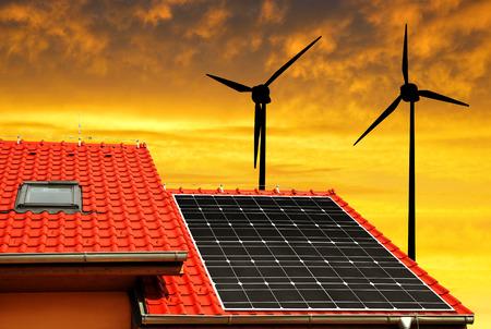 viento: El panel solar en el techo de la casa en las turbinas de viento en la puesta de sol de fondo.