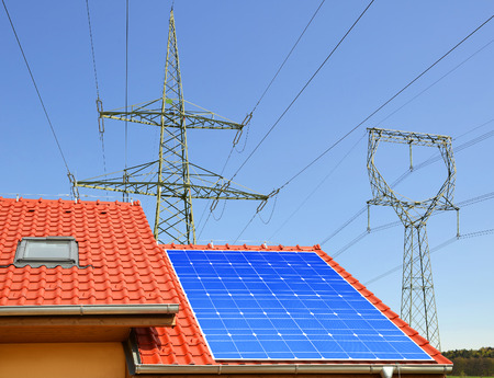 alternativ: Solar panel on the roof of the house in the background high voltage pylons Stock Photo