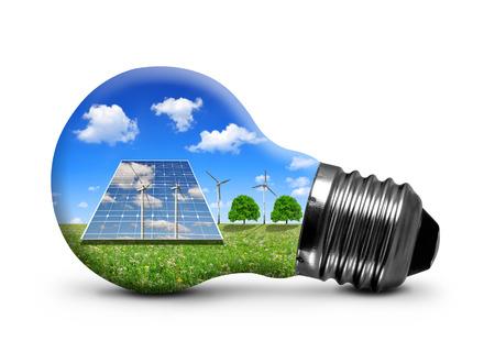PLACAS SOLARES: Los paneles solares y turbinas de viento en la bombilla aislados sobre fondo blanco. Concepto de energía verde. Foto de archivo