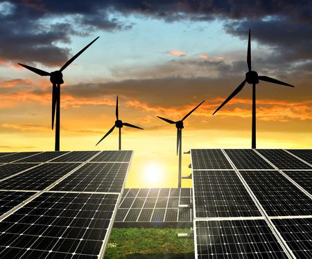 Solaranlagen mit Windkraftanlagen in der untergehenden Sonne