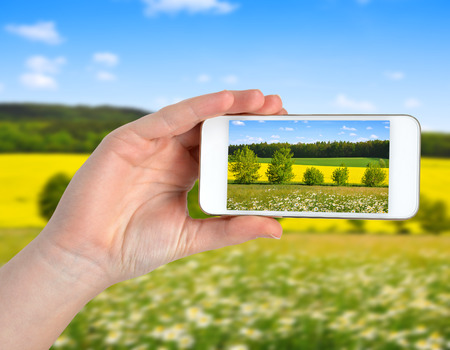 Hand taking photo of spring landscape by smartphone photo