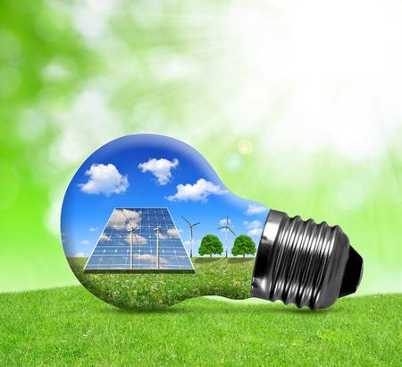 erneuerbar: Sonnenkollektoren und Windkraftanlagen in Glühbirne. Grüne Energie-Konzept.
