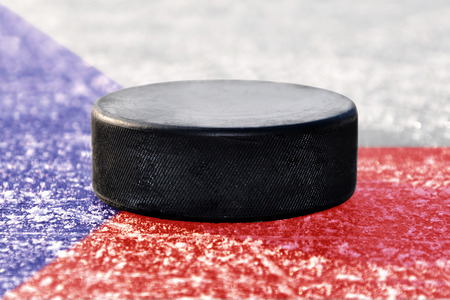 wintrily: Black hockey puck on ice rink with Czech flag.