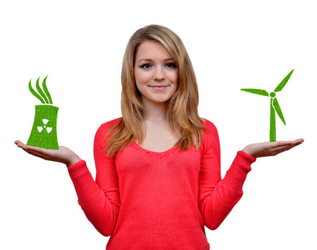 electricity generator: Girl holding in hands wind turbine and nuclear power plant icon.