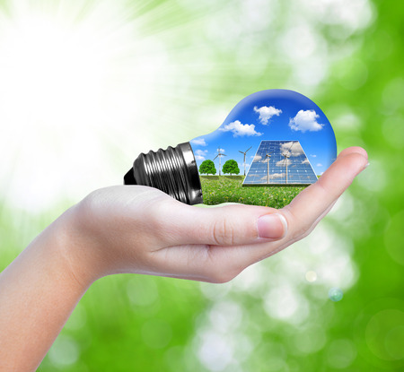 Hand holding eco light bulb on green