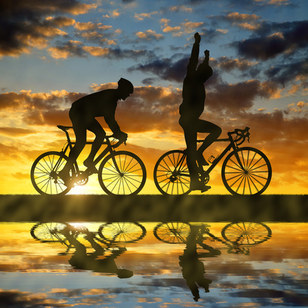 rapidity: silhouette of two cyclists riding a road bike at sunset
