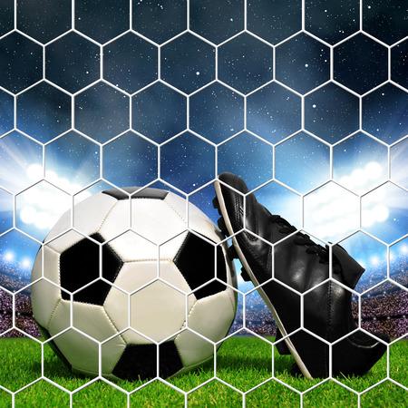 ballon foot: Soccer ball et des chaussures dans le stade de football de l'herbe avec les lumières. Banque d'images