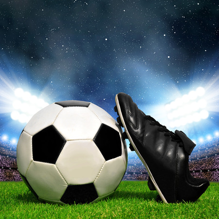 soccer cleats: Soccer ball and shoes in grass soccer stadium with the dright lights