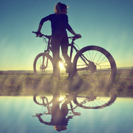mountain biker: Girl on a bicycle in the sunset Stock Photo