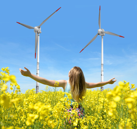 viento: Joven mujer feliz en campo floreciente colza en las turbinas de viento de fondo