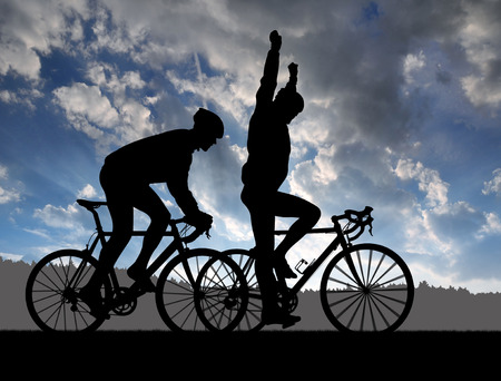 rapidity: Silhouette of the two cyclist riding a road bike at sunset