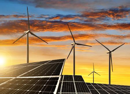 Solar panels with wind turbines in the setting sun Stockfoto