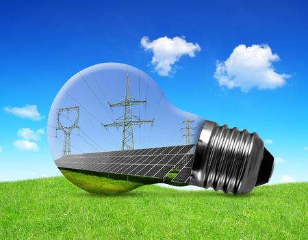 alternativ: Solar panels with pylons in light bulb. Green energy concept. Stock Photo