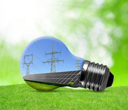 태양 전지 패널과 전구의 고전압 철탑. 녹색 에너지 개념.