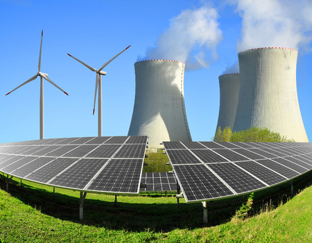 generator industry: Solar energy panels before a nuclear power plant and wind turbines Stock Photo