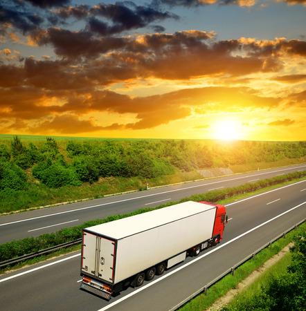 Vrachtwagen op de snelweg bij zonsondergang. Stockfoto