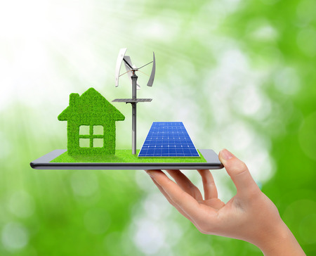 solar symbol: Hand holding tablet with green house, wind turbine and solar panel. Ecology concept.