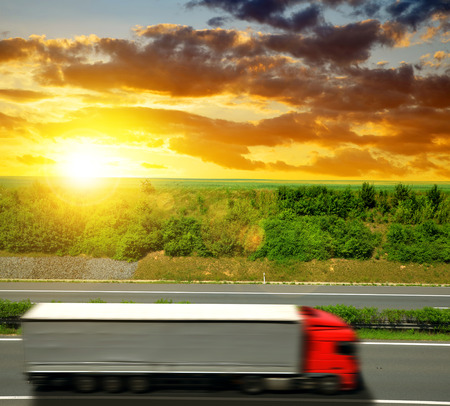 cary: Truck on the highway at sunset. Stock Photo