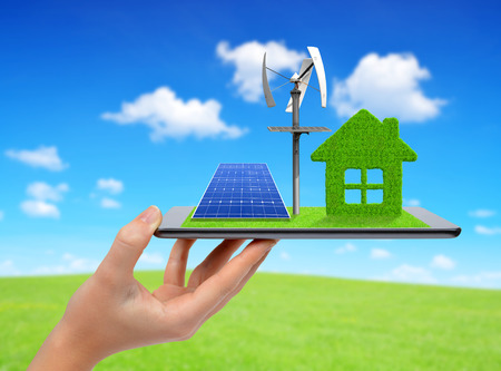 Hand holding tablet with green house wind turbine and solar panel. Ecology concept.