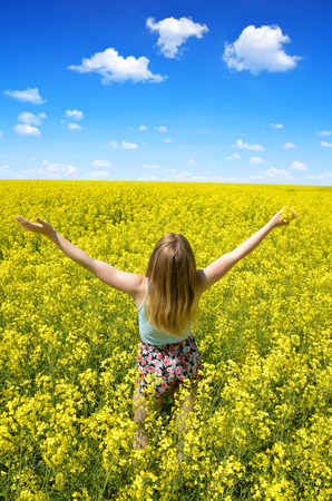 vitality: Young happy woman on blooming rapeseed field in spring