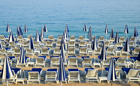 loungers: Sun loungers and a beach umbrellas on a beach. Vacation concept.