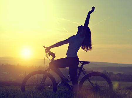 fin de semana: Muchacha con la bicicleta en la puesta de sol