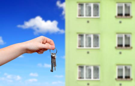 Hand met sleutels op de achtergrond flatgebouw Stockfoto