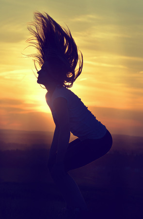woman sunset: Young woman jumping at sunset