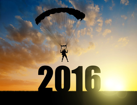 skydiver: Silhouette skydiver parachutist landing in the New Year 2016 at sunset Stock Photo