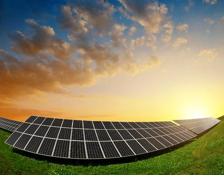 energy costs: Solar energy panels against sunset sky