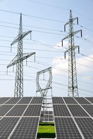 alternativ: Solar panels with electricity pylons. Green energy concept.