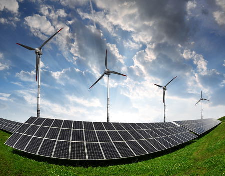 power of savings: Solar panels with wind turbines in the setting sun Stock Photo
