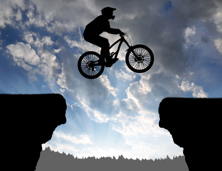 dramatic clouds: silhouette of biker jumps over the gap on the bike at sunset